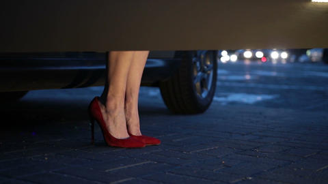 Woman's legs in heels stepping out of car at night