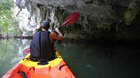 guy rows on kayak doing sport under stone icicles Footage