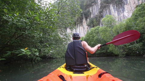 strong elder man floats kayak to gray cliff Live Action