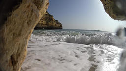 Waves to cam between rocks, loopable Footage