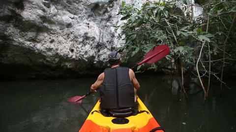 man rows kayak along river past cliff Footage
