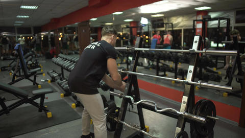 Personal trainer preparing training site for his clients in the gym, profession Footage