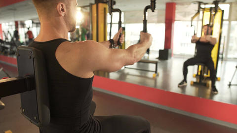 Man pumping his pectoral muscles in gym, looking at his reflection in mirror Footage
