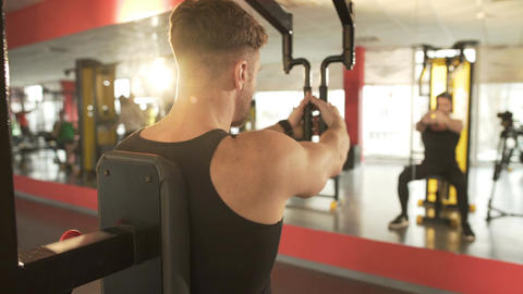 Male exercising on fly chest machine, working hard to achieve desired result Footage