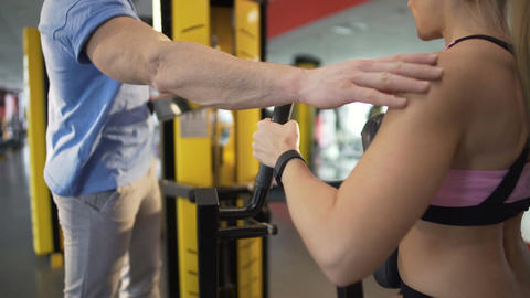 Fitness coach helping female client do exercises in gym, healthy lifestyle Footage