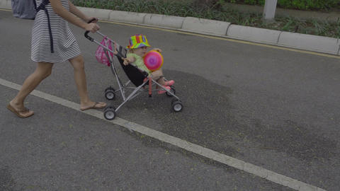 Woman walking with child in park of hotel Footage