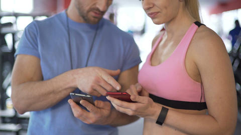 Sporty woman synchronizing schedule with her coach to work out more often Live Action