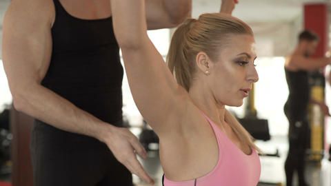 Personal trainer helping client to keep her posture while doing exercise in gym Footage
