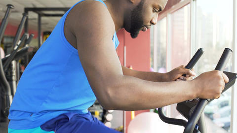 Motivated man riding a stationary bike, shaping up his body in the gym Footage