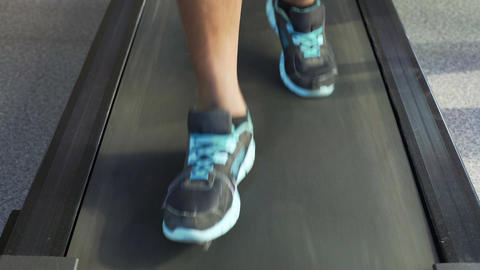 Legs of athletic male running on treadmill, cardio workout in the fitness club Footage