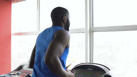 African-American male boxer running on treadmill and exercising in the gym Live Action