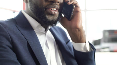 Pleased African-American man in suit talking on cellphone, making an appointment Footage