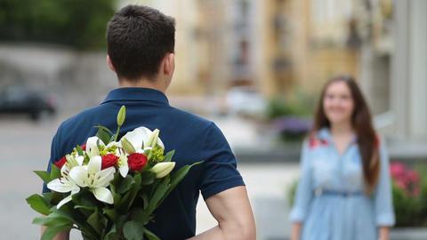 Young man hiding flowers for girl behind his back Footage