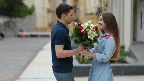Young man giving bunch of flowers to girl on date Footage
