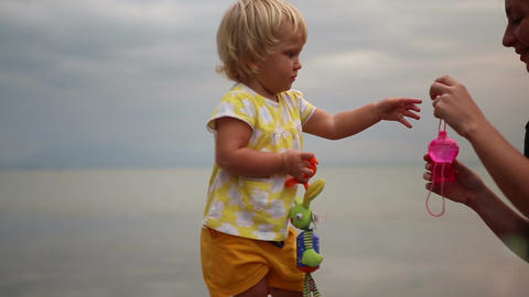 Little Blonde Child Comes up to Mother Blowing Soap Bubbles Footage