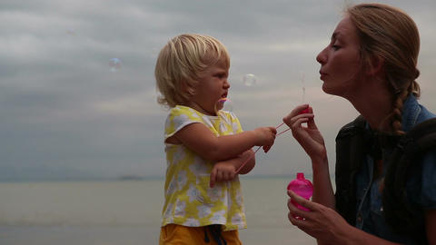 Little Blonde Child Play with Mother Blowing Soap Bubbles Footage