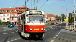 passing trams on the urban street - cars - buildings - nature (trees) - sunny -  Footage