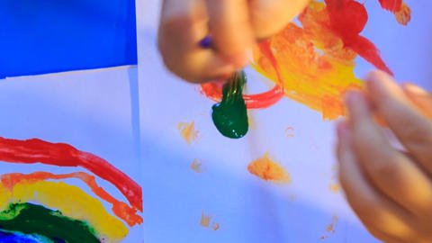 Kid's Hands Paint Green Spots with Brush on Paper Sheet Footage