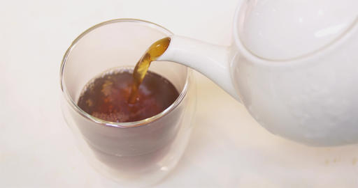 Close up pouring hot tea into a glass cup Footage