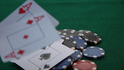 Placing 4 aces on a pile of poker chips Live Action