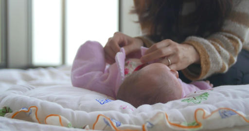 Moving shot of mother changing newborn babes clothes Footage