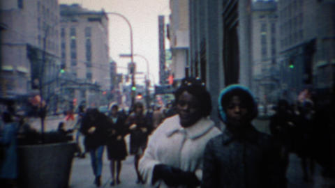1969: African family waiting on busy urban downtown sidewalk Live Action