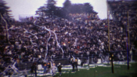1969: College football stadium crowd celebrating with toilet paper streamers Footage