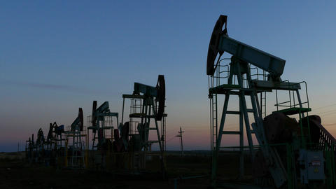 many working oil pumps silhouette in dusk, 4k Footage