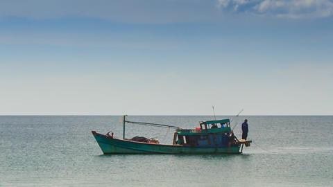 Vietnamese Fishing Boat Man on Stern Drifts along Sea Footage