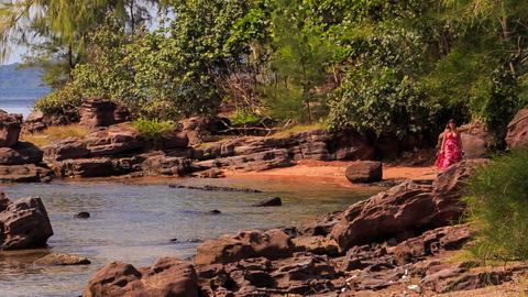 Blond Girl in Red Walks by Rocks along Beach with Plants Footage