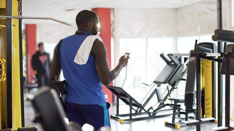 Handsome athletic man listening to music in gym, selecting song on smartphone Footage