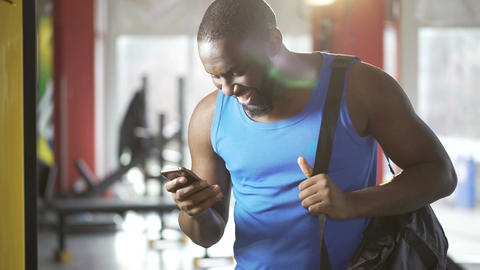 Successful young male chatting in smartphone app after workout, flirting online Footage