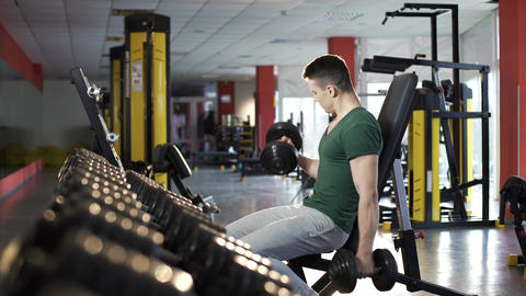 Handsome young man doing dumbbell exercises in gym, building muscular body Footage