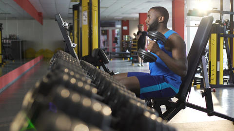 Male athlete exercising with dumbbells in gym, active healthy lifestyle, fitness Footage