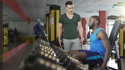 Supportive young man motivating friend during dumbbell workout in gym, fitness Live Action