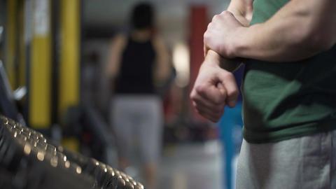 Male bodybuilder massaging arm, suffering wrist sprain during workout in gym Footage