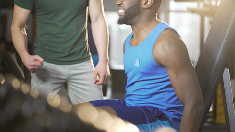 Friend supporting young man during difficult exercise in gym, giving high five Live Action