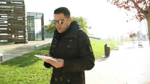 Lifestyle in the city Traveling modern park and man walking with tablet Footage