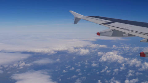 View from a plane window: a plane wing over clouds and blue sky Live Action