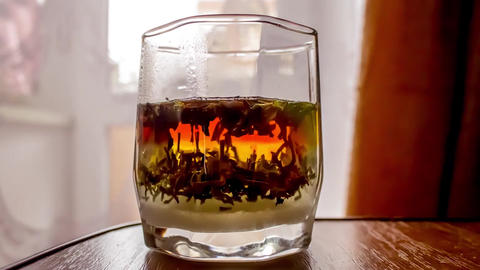 Black tea is brewed in a faceted glass Time lapse Stock Video Footage