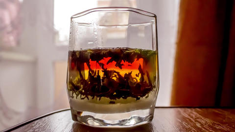 Black tea is brewed in a faceted glass Time lapse Footage