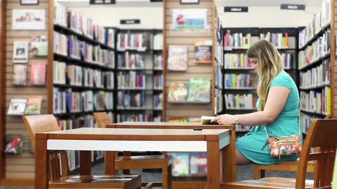 Wide shot of attractive blonde in library reading generic book Footage