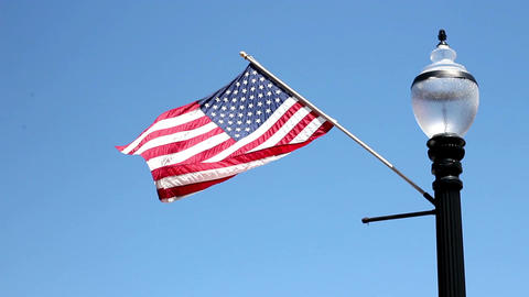 American Flag waving against clear blue on black lamppost Footage