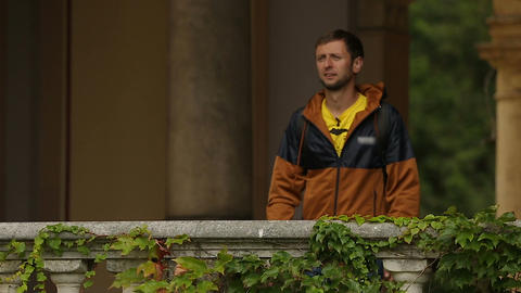 Tourists standing on balcony covered ivy and enjoying view on Mirogoj church Footage