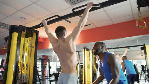 Athlete doing chin-ups, friend supporting and motivating him, giving high five Live Action