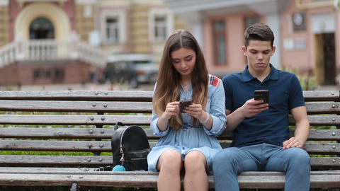 Couple in disinterest moment with phones outdoors Footage