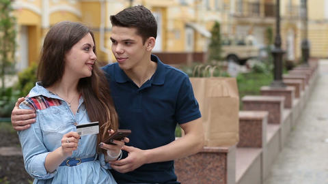 Couple making purchase online with phone outdoors Footage
