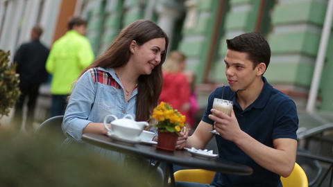 Young couple enjoying romantic date in street cafe Footage