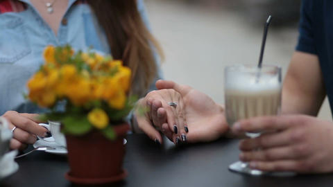 Young couple holding hands at the cafe, closeup Footage