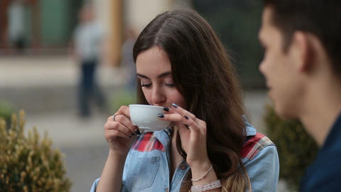 Smiling young woman drinking coffee at cafe Footage